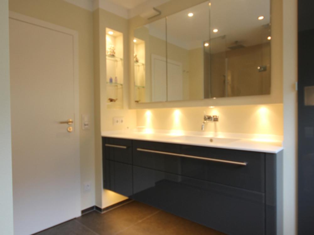 Badezimmer mit Mineralwerkstoff Waschtischplatte, Vola Armatur, Kerlite Fliesen, Einbau-Hängeschrank und Waschtisch-Unterschrank mit Glasfronten
