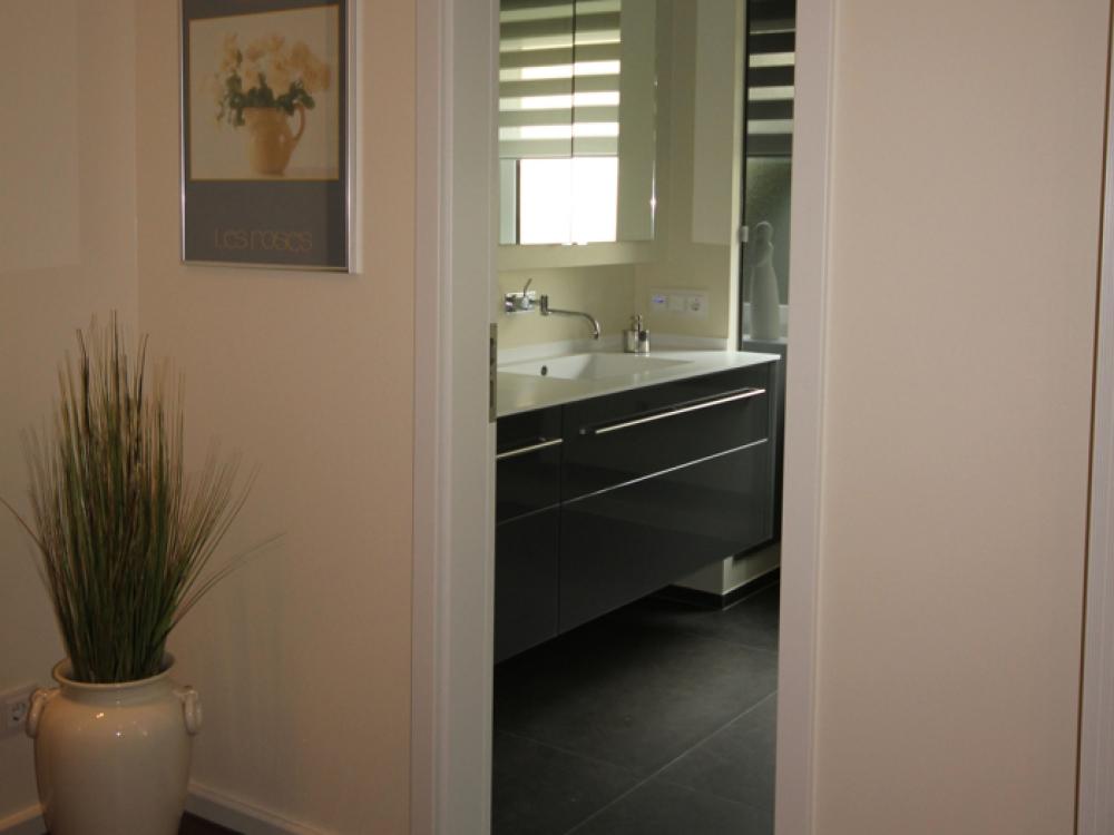 Blick vom Flur ins Badezimmer einen Waschtisch aus Glasfronten, Vola Armatur und Mineralwerkstoff Waschtischplatte